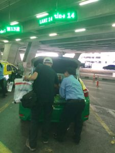 Taxi driver helping with luggage